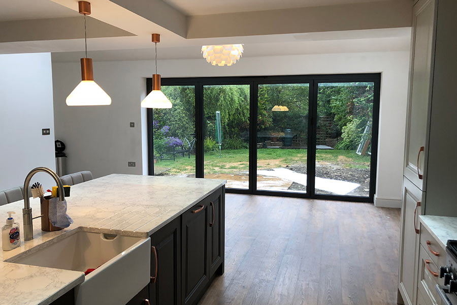 inside of a house extension with a new kitchen and aluminium bi folds doors